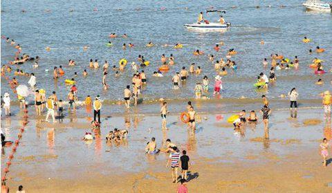 高温天气催热了滨海旅游,8月4日下午浙江温岭的一个海滨浴场游客